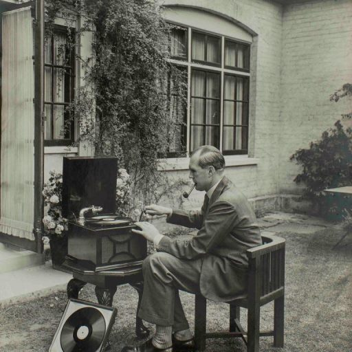 Un homme assis dans le jardin avec un phonographe et des disques sur une table. Il semble tourner la manivelle de l'appareil avant d'écouter son livre.