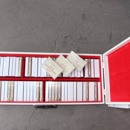 A long open oblong box with red lining and carrying handle, containing the 72 cassette tapes in two rows with three tapes laid on top to show the title - Old Testament
