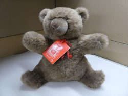 An upright seated brown bear with a product tag tied around it's neck