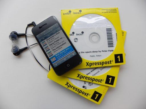 Un téléphone intelligent avec des écouteurs attachés se trouve au-dessus de trois CD de la Bibliothèque de l'INCA