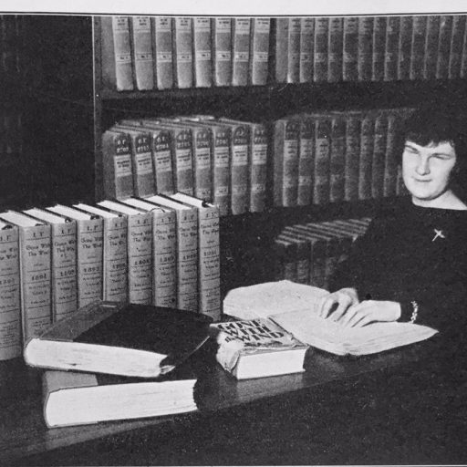 Woman reading a braille volume at a table with the print version of the book and eleven additional volumes of braille on the table