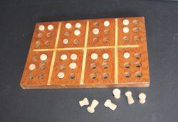 Une planche en bois avec 2 rangées pour créer quatre lettres en braille – de grandes chevilles en bois sont placées dans des trous pour créer des lettres.