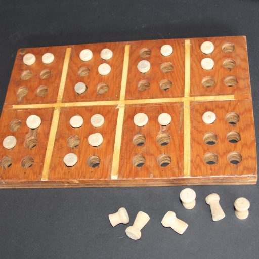 Wooden board with 2 rows for creating four braille letters - large wooden pegs are placed in holes to create letters