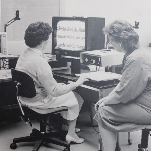 La cliente est assis devant l'écran, la main sur le document sur le scanneur. La formatrice est assise à la droite de la cliente.