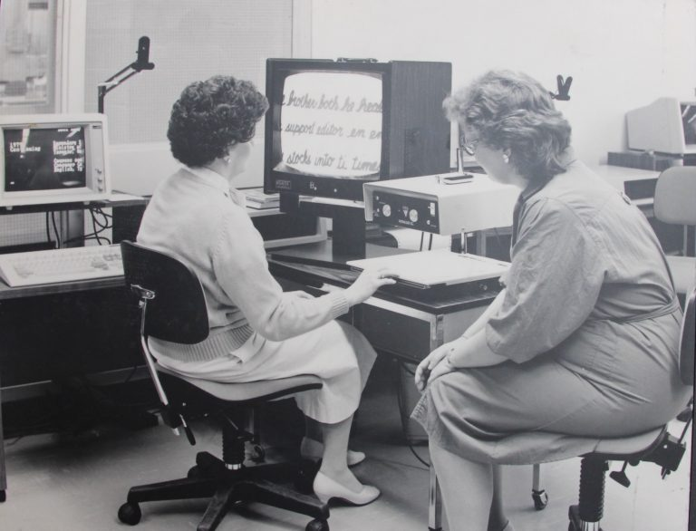 Client is sitting facing the screen and has her hand on the document on the scanner. Trainer is sitting on the right hand of the client. .