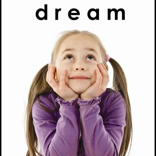 A young girl with elbows on the table is looking upwards, above her is the word dream and the braille equivalent