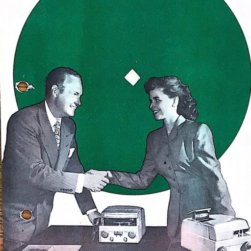 A man and woman shake hands with a Soundsciber on the table between them