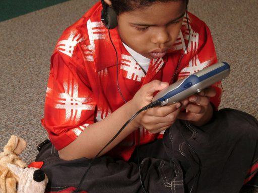 Un jeune garçon, assis sur le sol, les jambes croisées, porte des écouteurs et écoute un livre parlé sur un lecteur de CD. Sur le plancher, à côté du garçon, se trouve un jouet en peluche