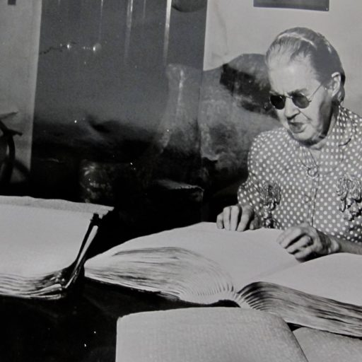 Miss Common sits at a table with three open, raised print books in front of her. Her hands are on one of the books
