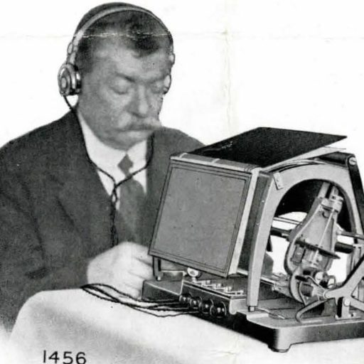 A man sits in front of an Optophone wearing connected headphones. An open book rests face downwards on the top of the equipment