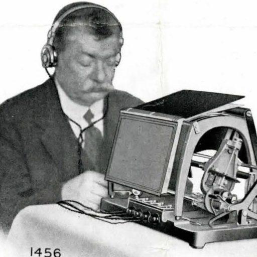 Un homme se trouve devant un optophone et porte un casque connecté. Un livre ouvert est placé face vers le bas sur de l'équipement.
