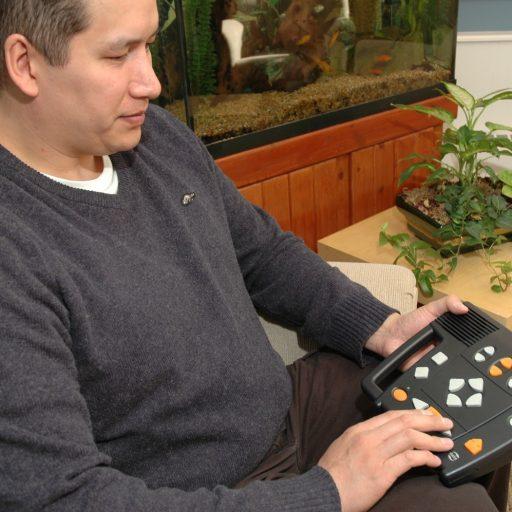 Un homme est assis sur un sofa avec le lecteur Victor Classic sur ses genoux.