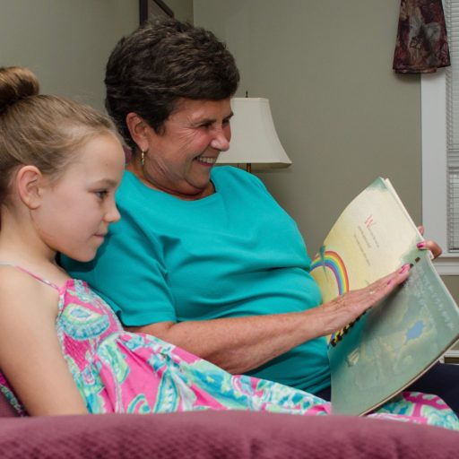 Woman and child sitting on a couch. The woman is using her right hand to read the braille on a clear interleaved page while the child looks at the pictures
