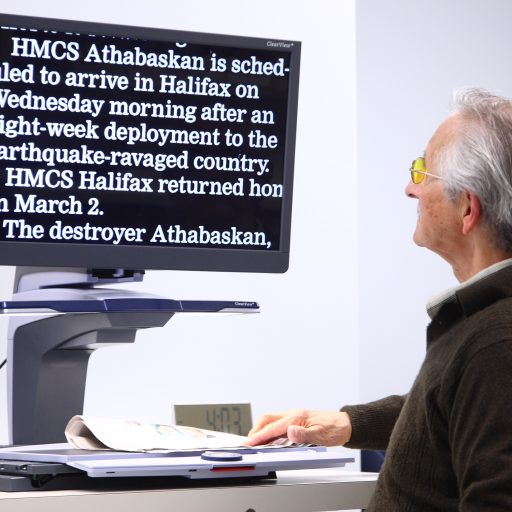 Man seated in front of a screen magnifier with the newspaper laid under a lens on the plate below. Text on the screen reads: HMCA Athabaskan is scheduled to arrive in Halifax on Wednesday morning after an eight-week deployment to the earthquake ravaged country. HMCS Halifax returned hom [sic] on March 2. The destroyer Athabaskan,