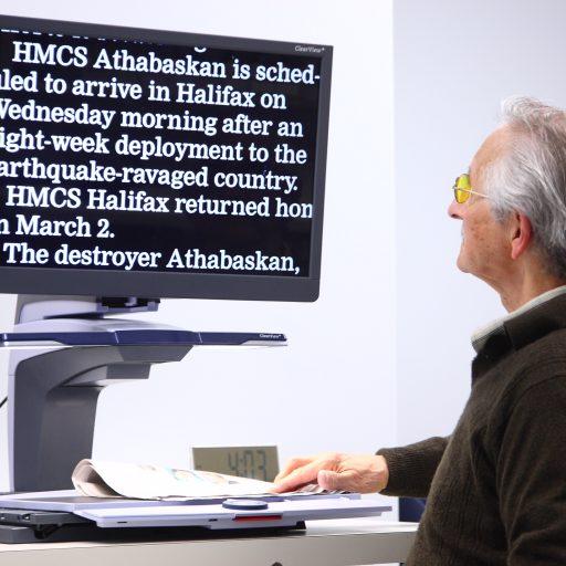 Un homme assis devant un agrandisseur d'écran avec le journal placé sous une lentille sur la plaque en dessous de l'écran. Le texte à l'écran est le suivant : Le NCSM Athabaskan devrait arriver à Halifax mercredi matin après un déploiement de huit semaines dans le pays ravagé par le séisme. Le NCSM Halifax est retourné chez lui le 2 mars. Le destroyer Athabaskan,