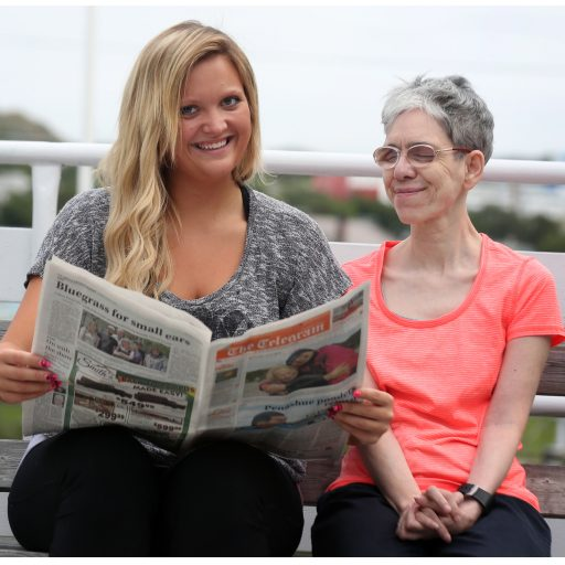 Two women sitting on a bench out-of-doors. On the left the vision mate is reading a newspaper, The Telegram, while the CNIB client listens.