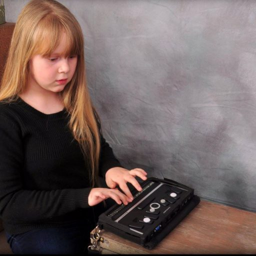 Young girl with her hands reading refreshable braille output