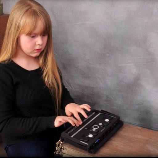 Une jeune fille avec ses mains en train de lire la sortie braille dynamique.