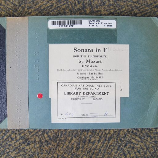 Music braille bound in a blue cardboard cover with braille title embossed and CNIB Library labels on the front cover.