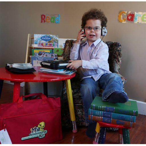 Un jeune garçon assis à une table muni d'un casque et d'un lecteur de livres parlés place sur la table. Il a placé l'un de ses pieds sur un tabouret par-dessus plusieurs livres; une mallette rouge intitulée « My Readasauraus Kit » (Ma trousse Readasaurus) contre le pied de table. En arrière-plan, sur le mur il y a les mots tactiles Read et Care et une étagère avec des livres gros caractères pour enfants.