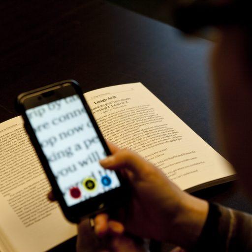 Un téléphone intelligent est tenu au-dessus d'un livre et une partie du texte est élargie sur l'écran.