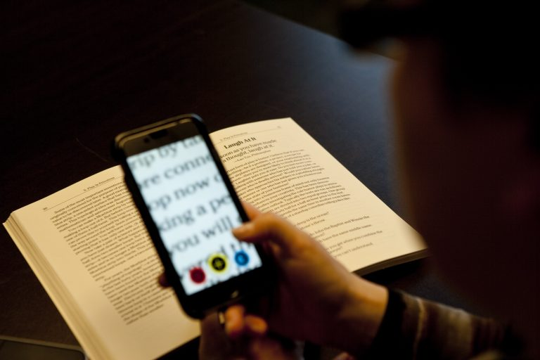 A smart phone is being held over a book and a portion of the text is enlarged on screen