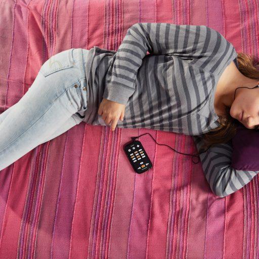 Une jeune fille se détend sur un sofa en écoutant un livre audio sur un lecteur Victor Stream.