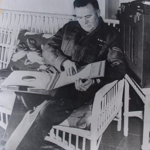 Man in uniform, sitting on a white wicker chair, has an open folder with multiple books on disk on his lap. His right hand is reading the braille on the first disk in the package