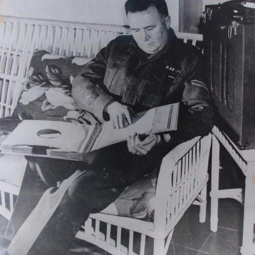Un homme en uniforme, assis sur une chaise en osier blanc, a un dossier ouvert comprenant plusieurs livres sur disque sur ses genoux. Sa main droite lit le braille sur le premier disque dans le dossier.