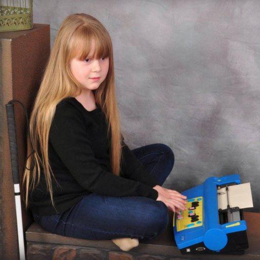 Une jeune fille assise, jambes croisées, devant le lecteur braille qui est de couleur bleu vive avec une partie jaune sur le dessus. Une connexion USB est visible sur le côté.