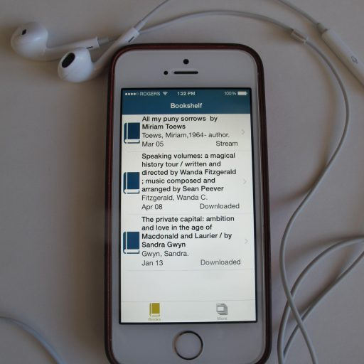 iPhone with ear buds attached. Screen shows user's current bookshelf of three books