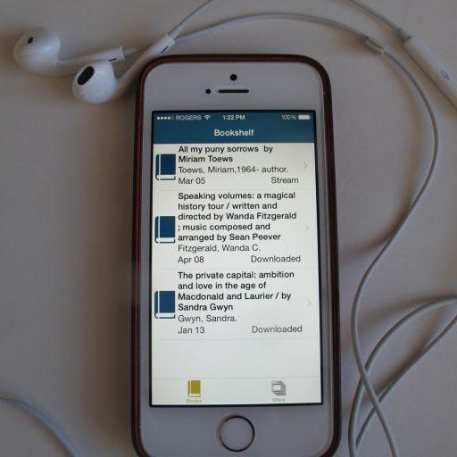 Un iPhone avec des écouteurs connectés. L'écran montre la bibliothèque actuelle de l'utilisateur avec trois livres.