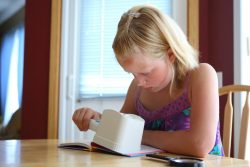 Child is sitting at a table reading a book with the assistance of a handheld magnifier with light
