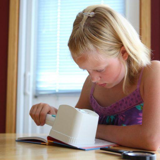 Une fille assise à une table, lisant un livre à l'aide d'une loupe de poche à éclairage.