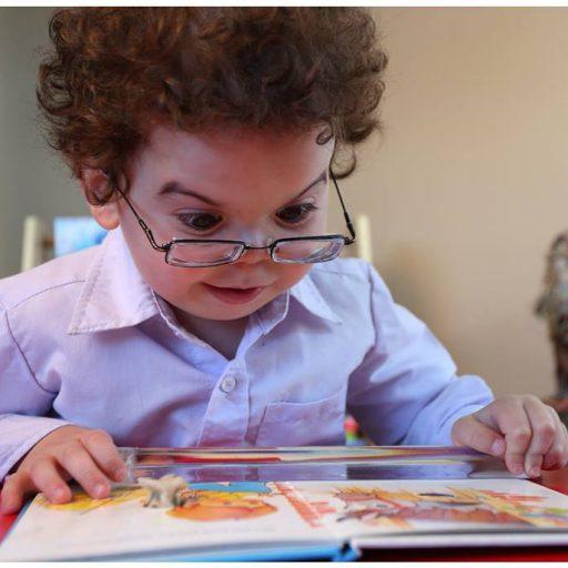 Un jeune garçon, portant des lunettes, tient une loupe pour la page sur un livre d'images ouvert et regarde attentivement l'image.