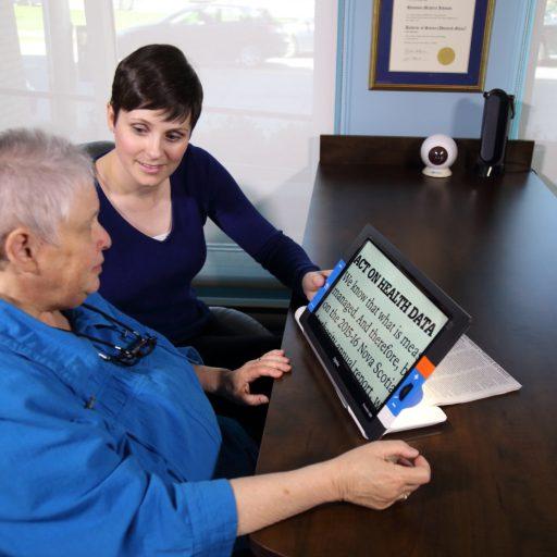 Une femme est assise à une table, avec la loupe électronique inclinée sur la table pour faire projeter une partie du document ci-dessous. Une femme est assise à côté d'elle pour l'aider ou l'instruire.