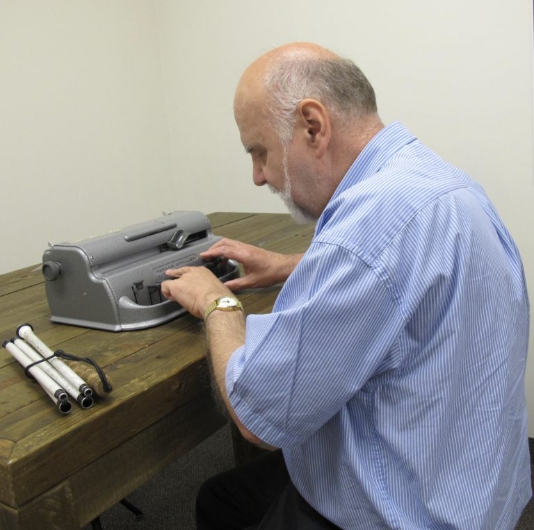 A man sits in front of the Perkins brailler with his hands on the keys. His folded white cane is on the table beside him