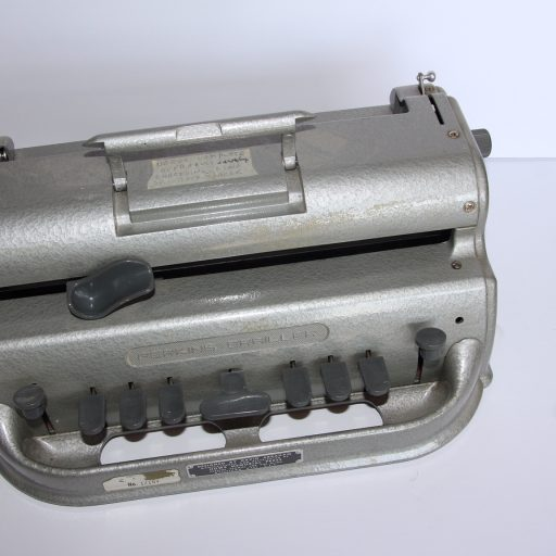 The brailler has 6 keys and space bar, a locking device to prevent paper from falling out of the machine, and a fixed carriage holding the paper