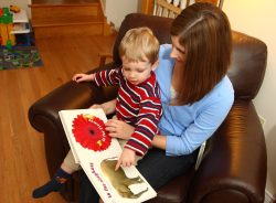 A woman is sitting with a young boy and an alphabet picture book on her lap. The boy is pointing to an elephant on the E page and the next page is F is for flower