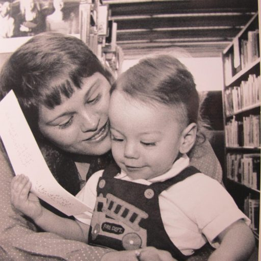 A mother has her arm around her child and is reading the braille from the book on his lap